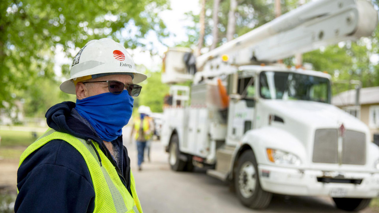 Maintaining social distancing and wearing protective masks adds to the challenge of restoring power to 128,000 customers. This scene was in Smackover Tuesday.