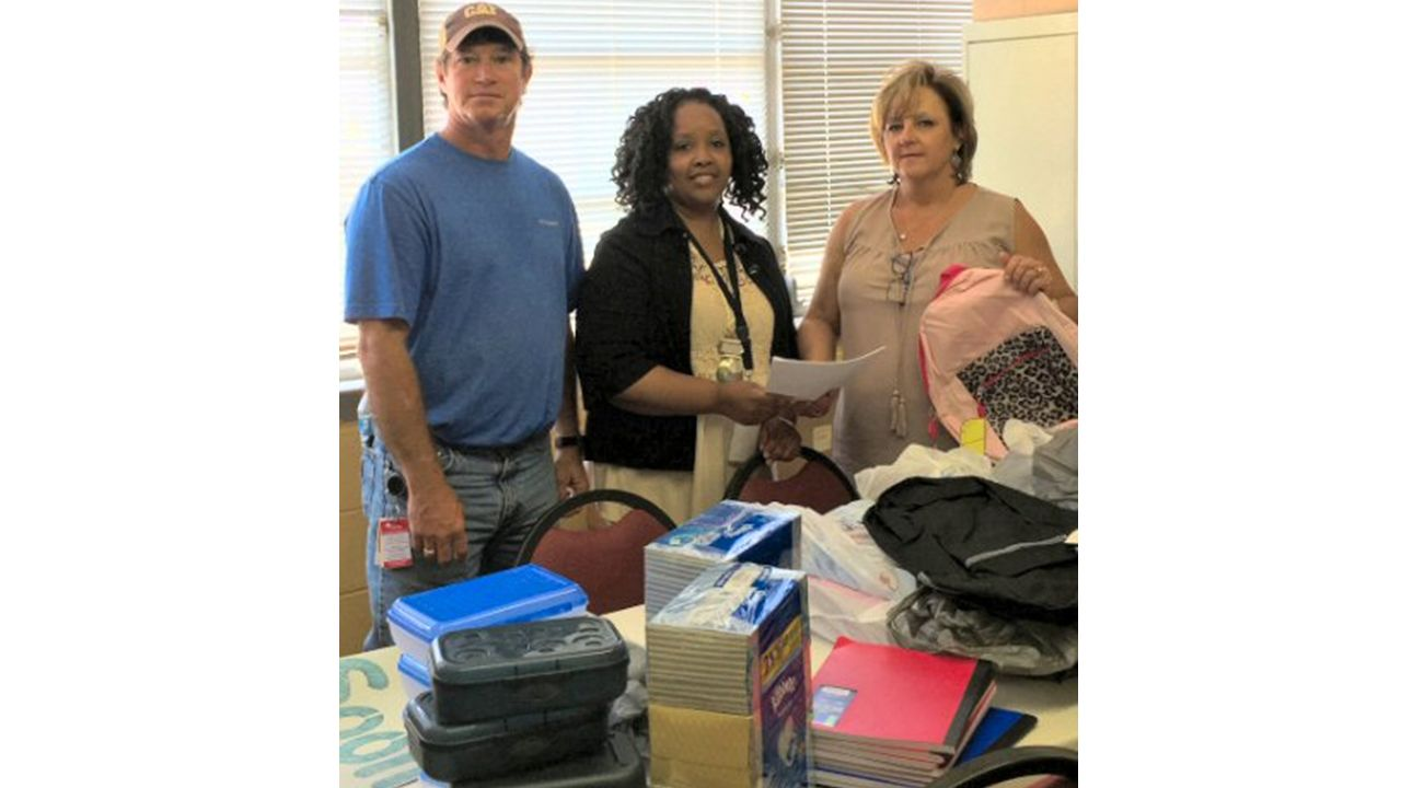 Mike Kyle, senior planner/scheduler, left, and Mary James, administrative assistant, right, deliver supplies to Amy Fleming, school secretary.