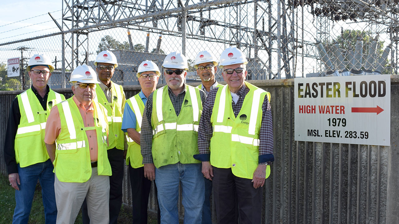 A group of employees and retirees who worked during the Easter Flood of 1979 gather at the Northeast Jackson Substation where a marker indicates how high the water level rose at that facility. From left Ed Smith, senior customer service representative, meter reading operations, Bob Hawkins, retiree, Louis Wright, customer service representative, Ken Coleman, retiree, Bill Bailey, serviceman, Darek Ashley, operations coordinator, and Don Meiners, retiree.