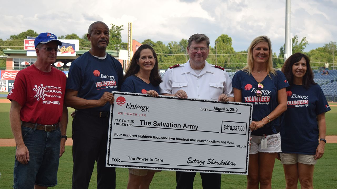 Entergy employees present Major Michael Hawley of the Salvation Army a check for The Power to Care program.